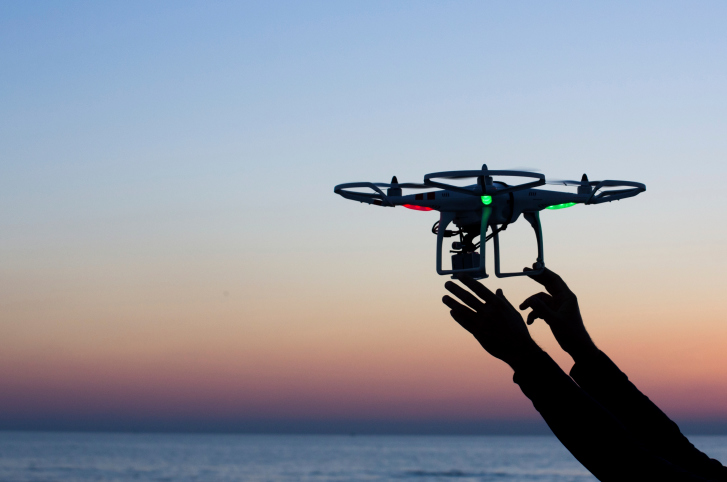 holding-up-drone-sunset-1 How Many Registered Drone Users in Your Area? Check out FAA's Database